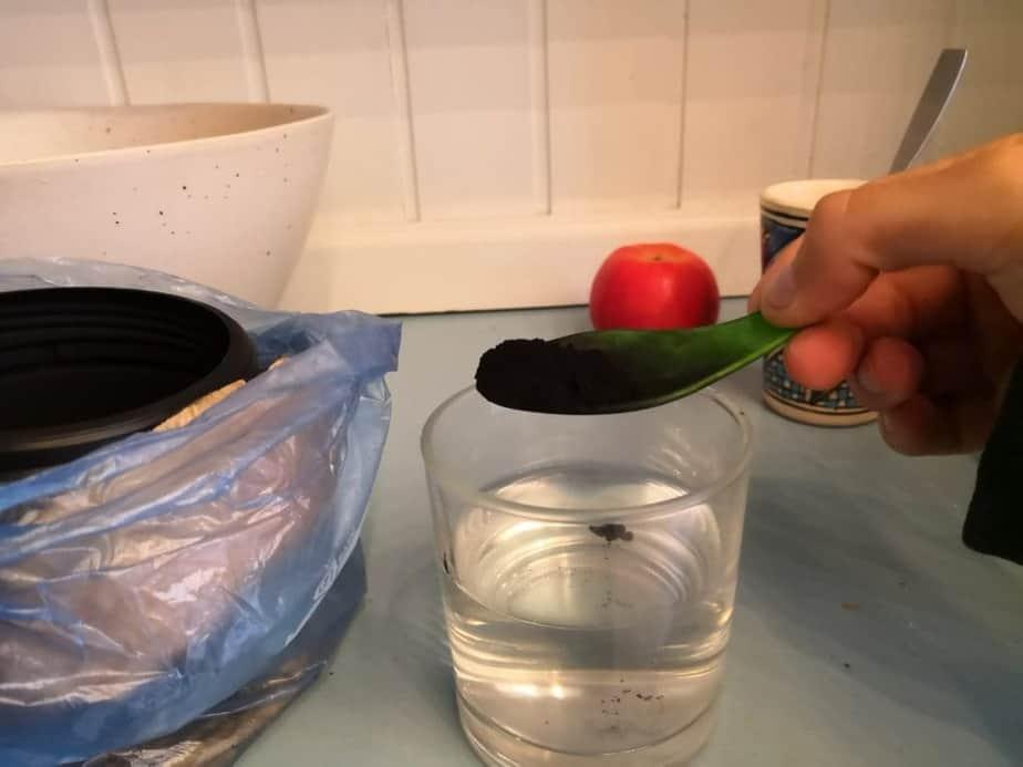 une cuillère de charbon actif dans un verre